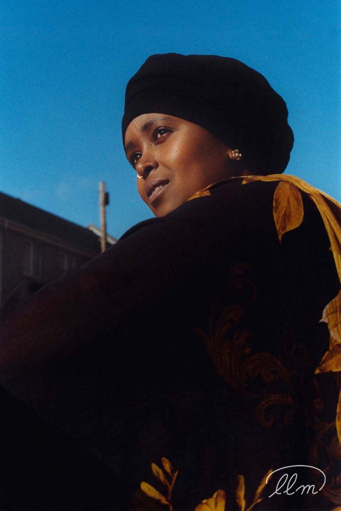Somali trader Amiira Ismail of Basbass Sauce, Lady Lane Market, portrait shot against blue sky