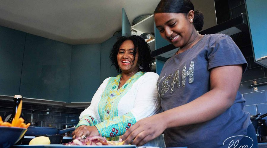 Lady Lane Market trader Woin Tegegn at home cooking for Ethiopic Kitchen - laughing with her daughter as they prepare food
