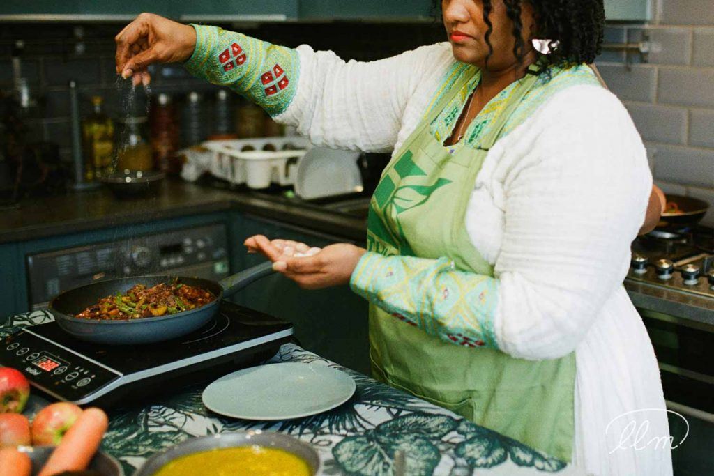 Lady Lane Market trader Woin Tegegn at home cooking for Ethiopic Kitchen - adding spices